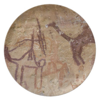 Prehistoric rock paintings with camels and dinner plate