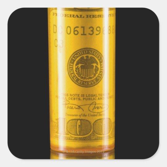 Prescription bottle with one hundred dollar bill square sticker