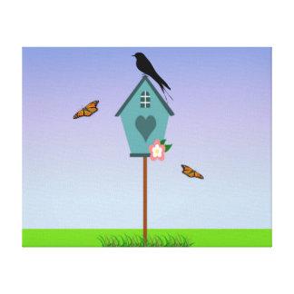 Pretty Bird Silhouette on top a Blue Birdhouse Canvas Print