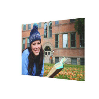 Pretty college student studying in autumn leaves stretched canvas print