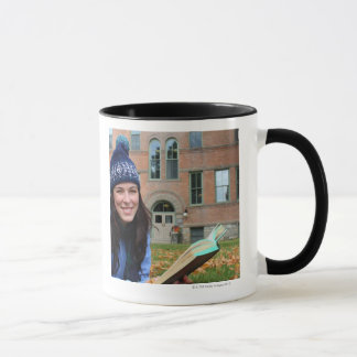Pretty college student studying in autumn leaves mug