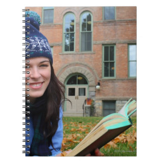 Pretty college student studying in autumn leaves notebook