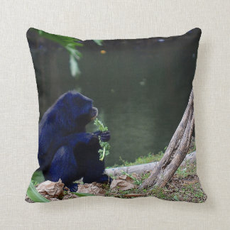Primate eating greens on edge of land blue throw pillow