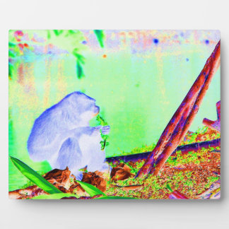 Primate eating greens on edge of land neon invert. plaque
