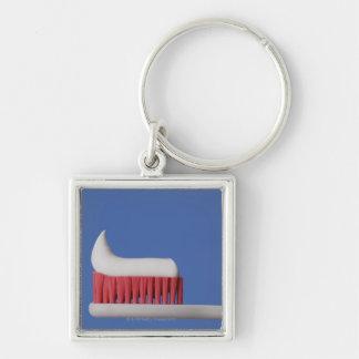 Primer de la crema dental en un cepillo de dientes llavero cuadrado plateado