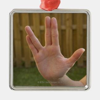 Primer de la mano de una mujer que hace una adorno navideño cuadrado de metal