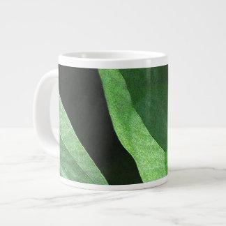 Primer de las hojas en luz y sombra taza de café grande