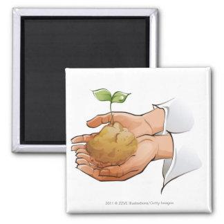Primer de las manos de una persona que sostienen e imanes para frigoríficos
