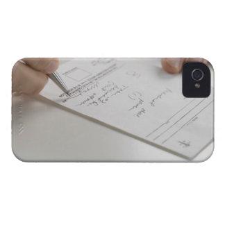 Primer de las manos que firman la prescripción carcasa para iPhone 4