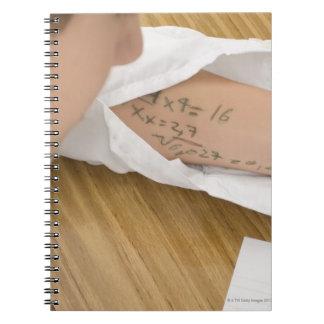 Primer de un colegial que copia en libro de apuntes con espiral
