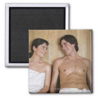 Primer de un par joven que se sienta en una sauna imán de frigorífico