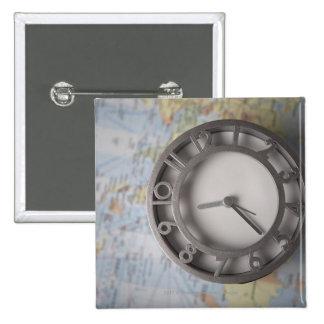 Primer de un reloj delante de un mapa pin cuadrado