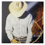 Primer de un vaquero que ata una rienda azulejos