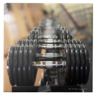 Primer de una fila de pesas de gimnasia azulejo cuadrado grande