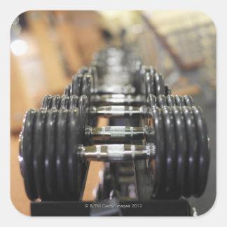 Primer de una fila de pesas de gimnasia pegatina cuadrada