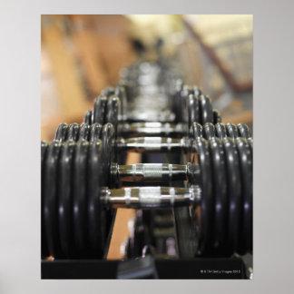 Primer de una fila de pesas de gimnasia póster