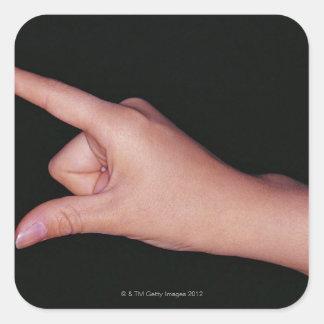 Primer de una mano con el dedo y el pulgar pegatina cuadrada