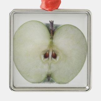 Primer de una manzana cortada del granny smith adorno navideño cuadrado de metal