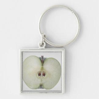 Primer de una manzana cortada del granny smith llavero cuadrado plateado