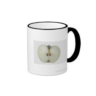 Primer de una manzana cortada del granny smith taza de café