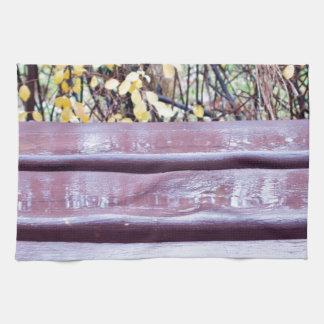Primer del banco de madera con los charcos después toallas de mano