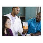 Profesor africano y estudiantes que miran el tarjeta postal