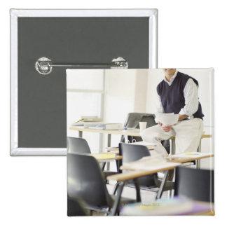 Profesor confiado que se inclina en el escritorio pin cuadrado
