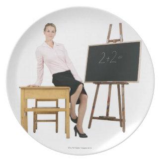 Profesor de sexo femenino que presenta por el escr platos de comidas
