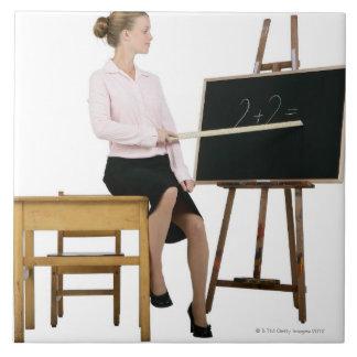Profesor de sexo femenino que señala la regla en l tejas