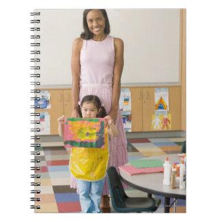 Profesor del cuarto de niños del chica (3-5) con cuaderno