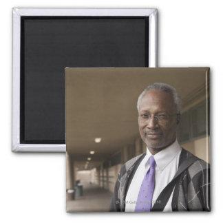 Profesor negro que se coloca en pasillo de la escu imán cuadrado