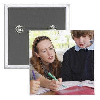 profesor que ayuda al niño con el trabajo en sala  pin cuadrada 5 cm