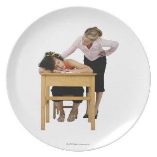 Profesor que comprueba el estudiante dormido en el platos