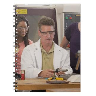 Profesor que demuestra el tenedor de herramienta cuadernos