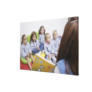 Profesor que lee a los estudiantes impresión en lienzo