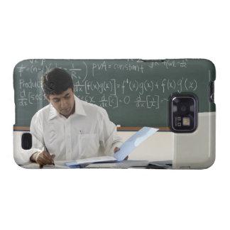 profesor que se sienta en el escritorio, trabajand galaxy SII carcasas