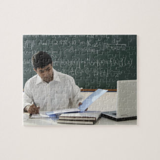 profesor que se sienta en el escritorio, trabajand rompecabeza con fotos