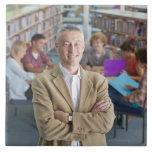 Profesor sonriente que se coloca en biblioteca esc teja cerámica