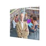 Profesor sonriente que se coloca en biblioteca esc impresión en lona