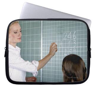 profesor y chica joven delante de la pizarra manga portátil