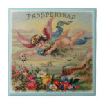 """Prosperity Angel prosperidad tile<br><div class=""""desc"""">A vintage image of an angel flying and scattering flowers over a scene which includes a train,  ship and flowers. The Spanish word for prosperity (prosperidad) is written above</div>"""