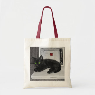 Prunella black cat lounging on laptop tote bag