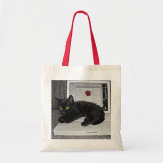 Prunella black cat lounging on laptop tote bag