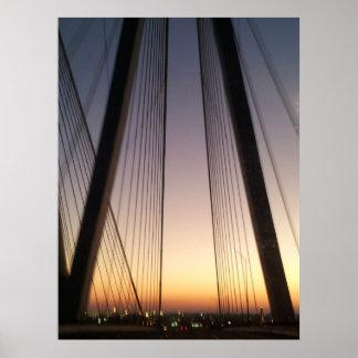 Puente colgante de la travesía en la puesta del so póster