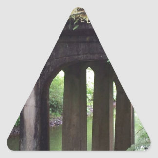 Puente cubierto de musgo sobre el río del pegatina triangular