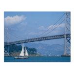 Puente de la bahía de Oakland con el velero, San F Tarjetas Postales