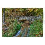 Puente de piedra en tarjeta del otoño
