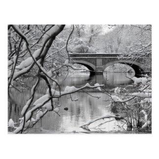 Puente del arco sobre el río congelado en invierno postales