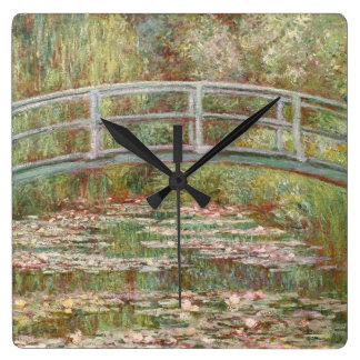 Puente sobre una charca de los lirios de agua reloj