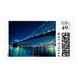 Puente y Lower Manhattan de Brooklyn en la noche Sello